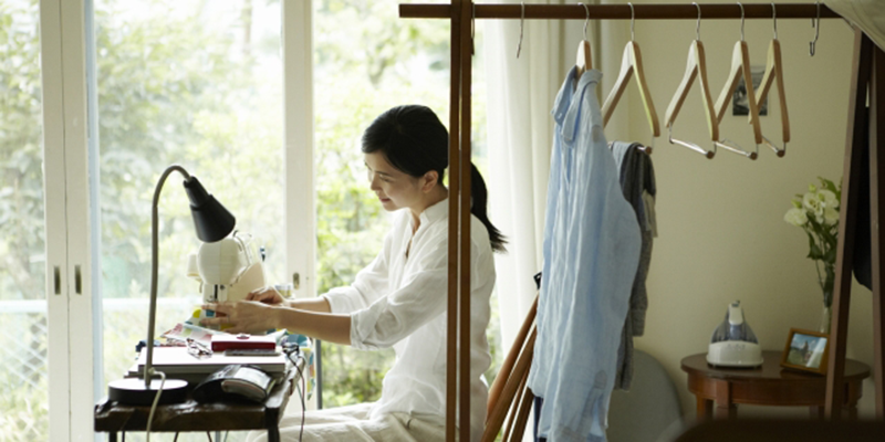 自宅でミシンで裁縫を行う女性